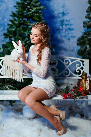 witchery: Red-haired girl holding a white Bunny, winter scenery