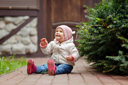 Very charming beautiful little girl with big brown eyes sits and smiles on the background of wooden houses and trees in autumn Stock Photo