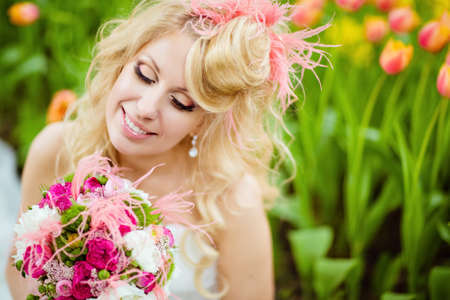 dress form: Portrait of a very beautiful bride blonde in a white dress with an unusual stylish hairstyle in the form of hats, sitting next to tulips and smiling, close up with her eyes closed