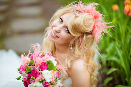 dress form: Portrait of a very beautiful bride blonde in a white dress with an unusual stylish hairstyle in the form of hats, sitting next to tulips and smiling, close up