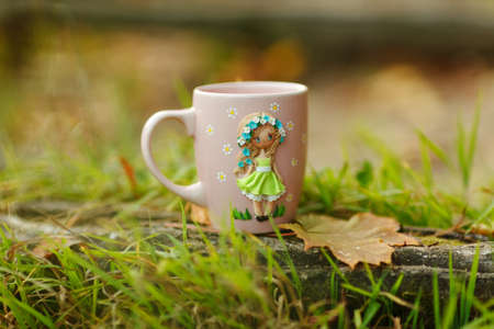Pink mug with decorations in the form of a girl in a dress made of polymer clay on nature background