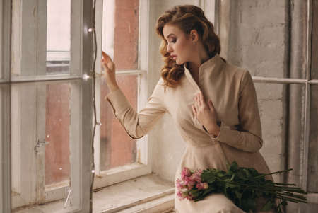Portrait of a beautiful delicate sensual blonde girl with roses sitting on window and looking into the distance
