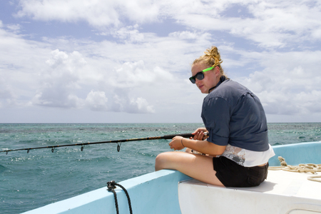 Woman fishing in the ocean on a boat