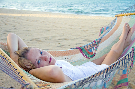 Beautiful woman lying in a hammock on a beach next to the ocean