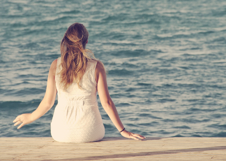 Woman in a white dress sitting on a wooden dock looking out at ocean Stock Photo