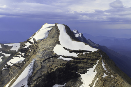 Mountain peak in Glacier National Park, Montana with stormy skies in the background
