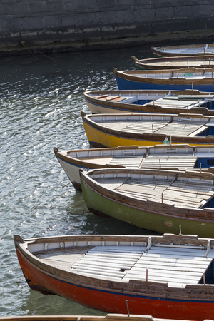 Row of colorful rowboats anchored in the Bay of Naples, Campania, Italy