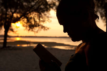 Silhouette of a woman sitting on the beach and reading a book Stock Photo - 5679245