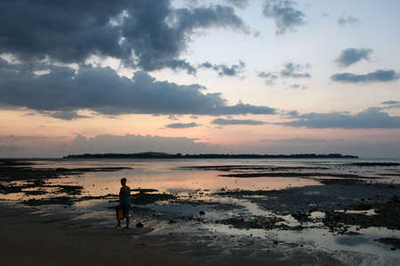 Woman is walking during the sunset on a tropical beach. Island Gili Meno in the background Stock Photo