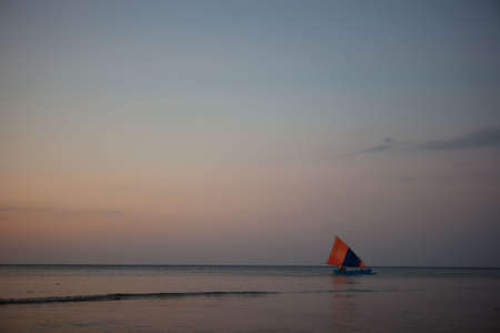 Single boat on the ocean during the sunset Stock Photo