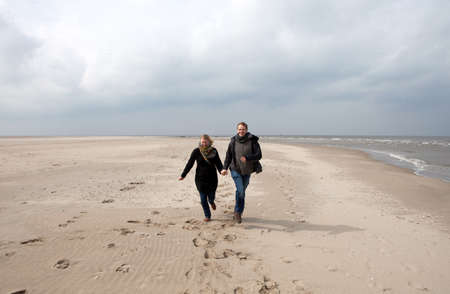 A young couple is running happy on the beach