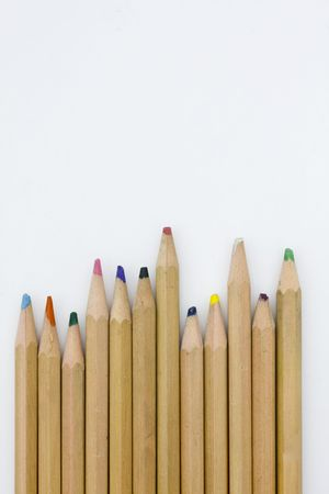 Colored pencils forming a color row. White background. photo