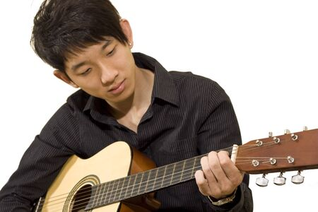 asia boy plays his guitar  Stock Photo - 7359589