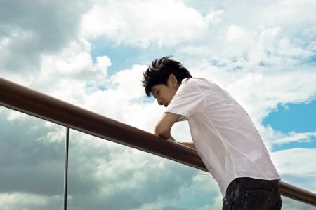 Ragazzo triste mano sullo sfondo del cielo e corrimano