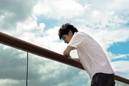 emotional: Sad boy hand on the handrail and sky background
