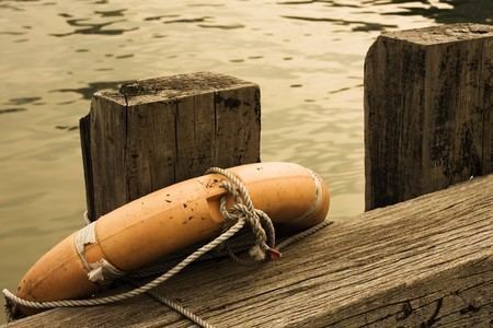 Lifebuoy on a wood in a dock ,close up photo