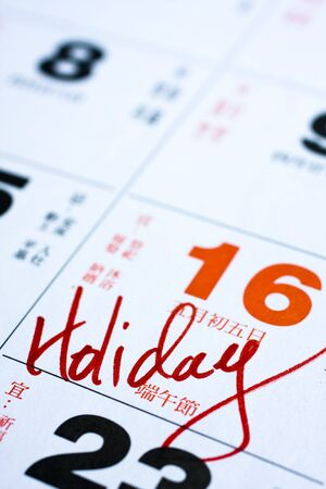 Hand writing holiday important date on calendar. photo