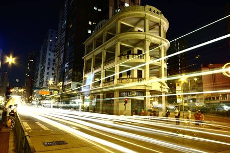 Fast moving cars at night in downtown photo