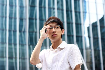 asian businessman holding glasses and modern building  Stock Photo - 7961174