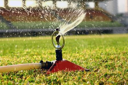 sprinkling: Water jets sprinkling stadium field.