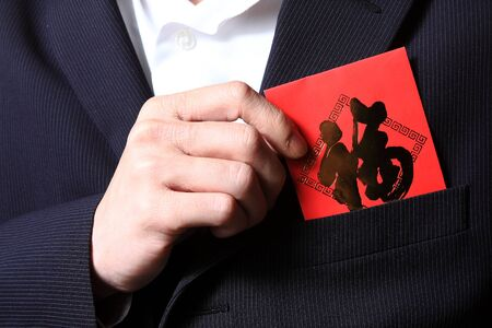 businessman putting chinese cash gift in his pocket photo