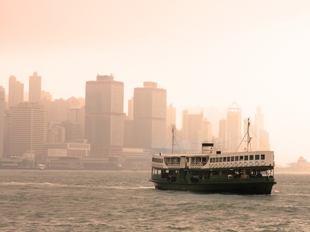 Famous landmark of Hong Kong ferry sailing on Victoria Harbor, Asia.  photo