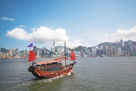 Junk boat with tourists in Hong Kong Victoria Harbour photo