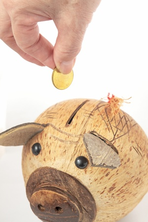 Saving, male hand putting a coin into piggy bank.  photo