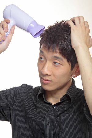 dryer: Concept image of metrosexual male featuring a young male using a hair dryer to fix his hair nicely Stock Photo