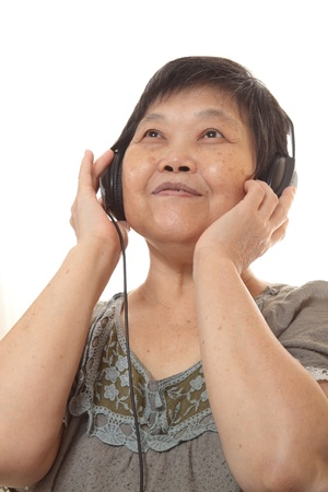 Senior woman listening to music with headphones  photo