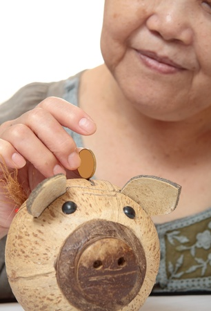 parsimony: woman putting coins in small piggy bank. Selective focus, Copy space