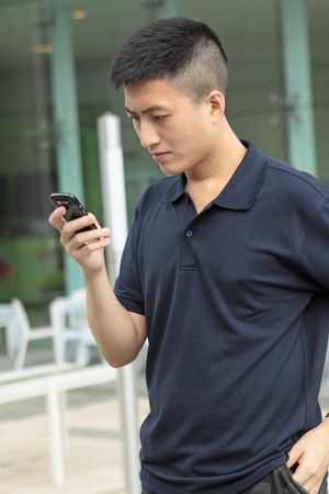 Asian man typing a message on mobile phone. photo