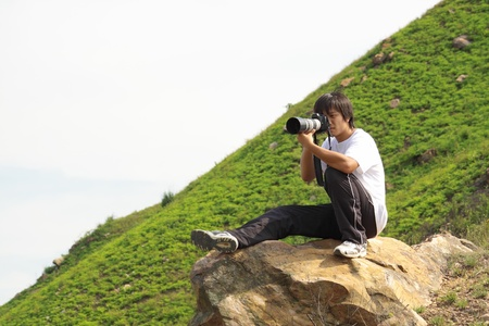 photographing: asian man taking photo in hiking Stock Photo