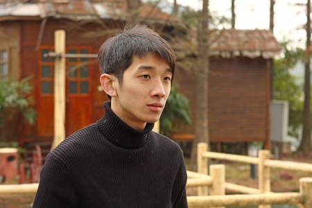 Asian man stand against a old house  photo