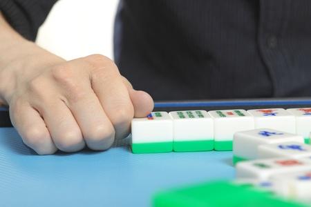 Chinese man play Mahjong, traditional China gamble.  photo