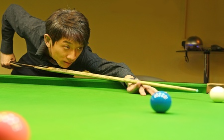 pool table: Young man concentrating while aiming at pool ball while playing billiards.