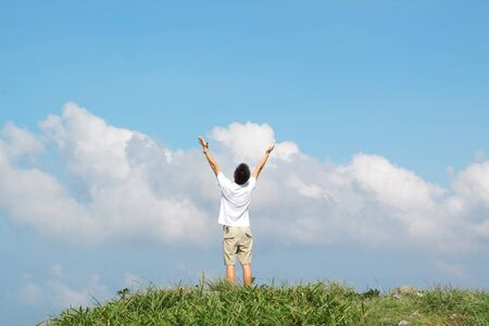 back up: Meeting of the sky. The man on high mountain with the hands lifted above, on a background of blue sky