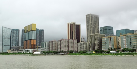 dwell house: Macau cityscape with famous casino skyscraper under cloudy sky.