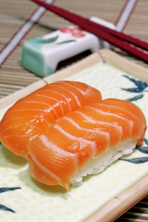 Yummy salmon. A close-up of chopsticks and a square plate with two pieces of salmon nigiri, wasabi and ginger.  photo