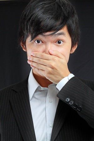 man mouth: scared adult man with hand covering mouth