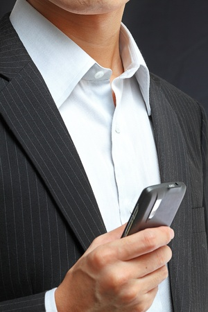 personal digital assistant: business man in black suit working on pda or smartphone