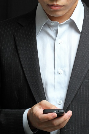 personal assistant: business man in black suit working on pda or smartphone