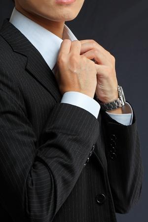 Einstellung junger Mann seinen Anzug auf einem schwarzen Hintergrund