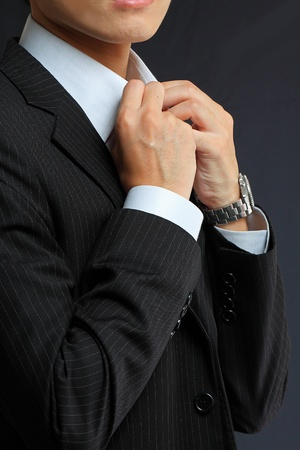 young man adjusting his suit on a black background