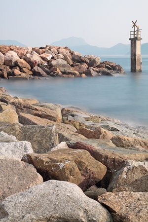 warns: Lighthouse on a Rocky Breakwall: A small lighthouse warns of a rough shoreline.  Stock Photo