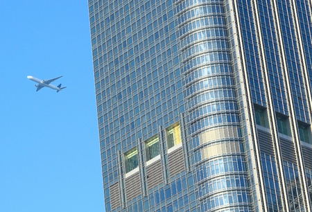 airplane fly over the modern building photo