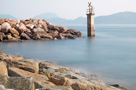 warns: Lighthouse on a Rocky Breakwall: A small lighthouse warns of a rough shoreline.  Editorial