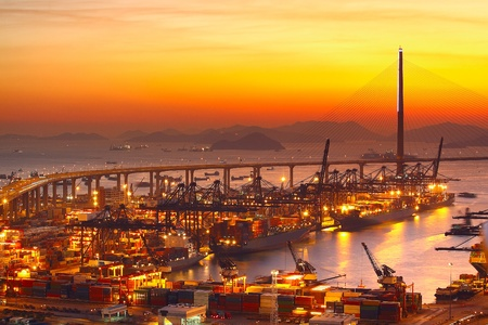 Port warehouse with cargoes and containers at sunset Editorial