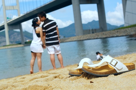 modern couple kissing each other on beach , foucs on shoe photo