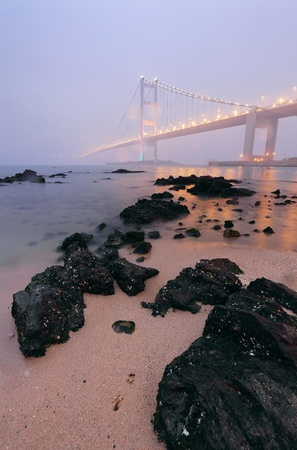 rocks on the beach and bridge in mist photo